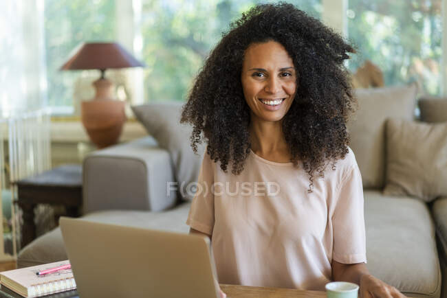 Smiling female entrepreneur sitting in living room at home — Stock Photo