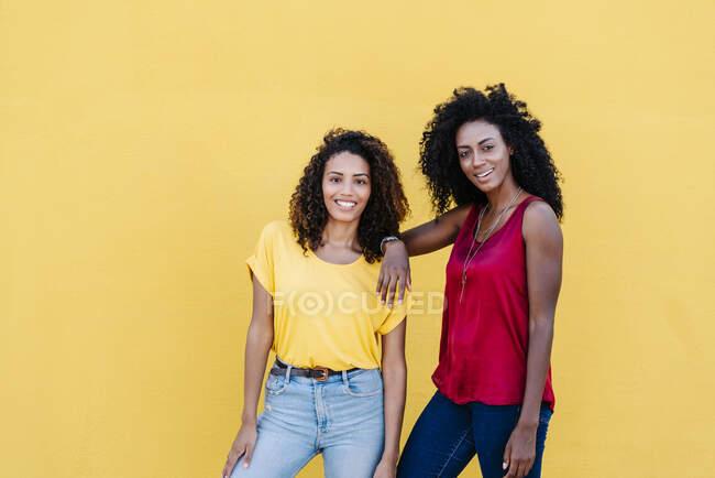 Couple lesbien souriant avec une attitude cool contre le mur jaune — Photo de stock