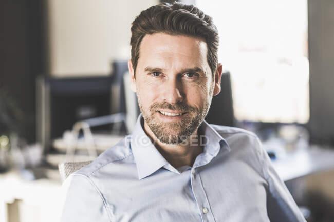 Maturo uomo d'affari sorridente mentre seduto a ufficio — Foto stock