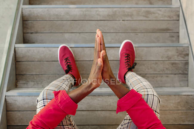 Young man in red jacket and checked pants sitting on steps outdoors — Stock Photo