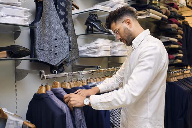 Camicie di navigazione dei clienti su rack in boutique sarti — Foto stock