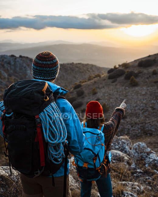 Fidanzata che indica la montagna durante le escursioni con il fidanzato durante il tramonto — Foto stock