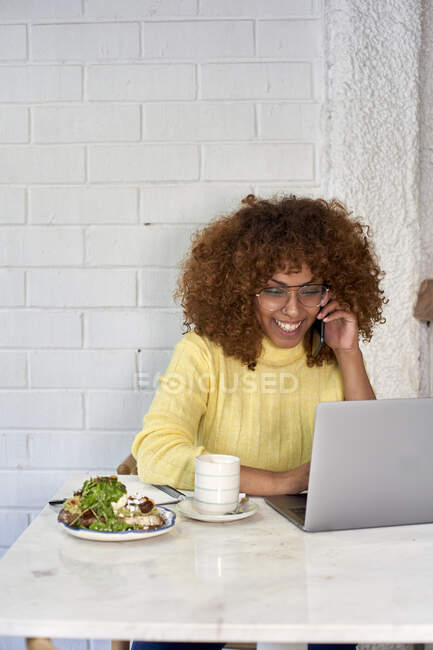 Smiling freelance worker with food and drink talking on phone call in cafe — Stock Photo