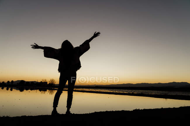 Young woman with arms outstretched standing by river during dusk at Ebro delta, Spain - foto de stock