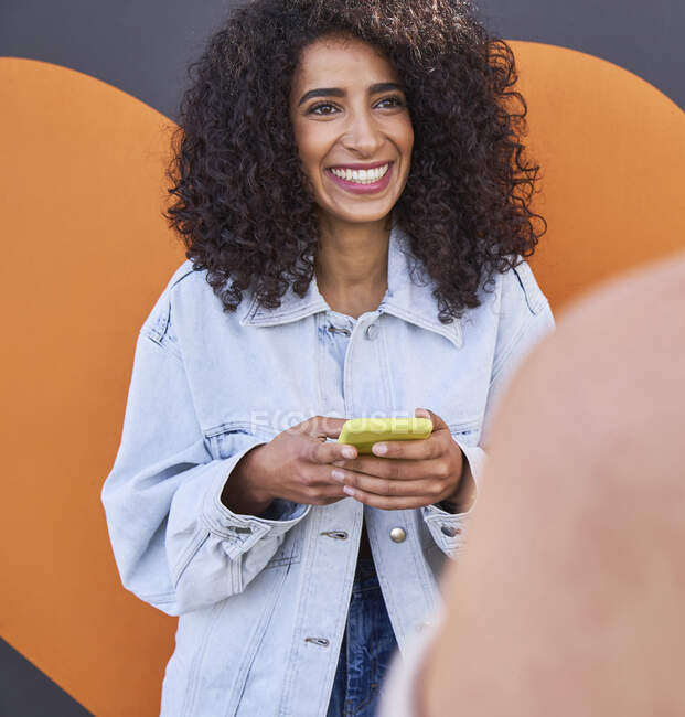 Smiling woman holding mobile phone talking with female friend while standing against wall — Stock Photo