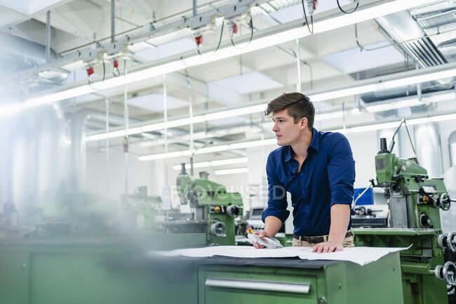 Engenheiro masculino com plano de chão e parte da máquina olhando para longe na fábrica — Fotografia de Stock