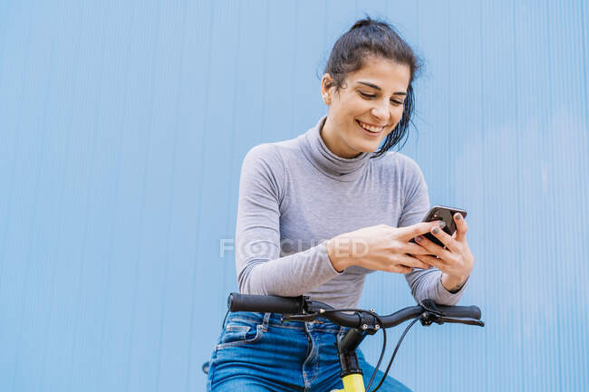 Cheerful beautiful woman using mobile phone while sitting on fixie bike against blue wall — Stock Photo