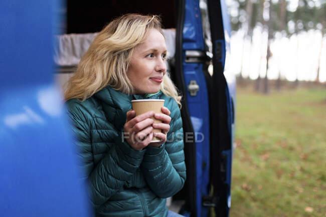 Mulher atenciosa com copo de chá descartável olhando para a porta do motor para casa — Fotografia de Stock