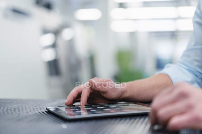 Male professional using digital tablet on desk in industry — Stock Photo