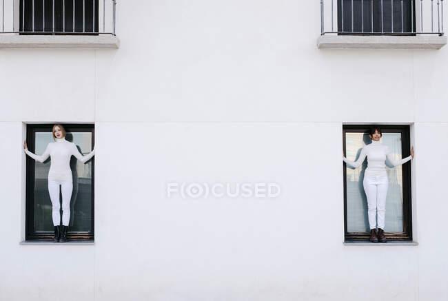 Mujeres jóvenes de pie en las ventanas del edificio blanco durante COVID-19 - foto de stock