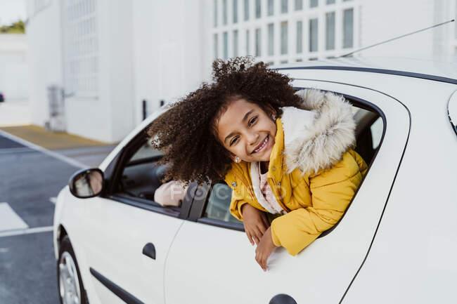 Cheerful girl peeking through window while traveling in car — Stock Photo