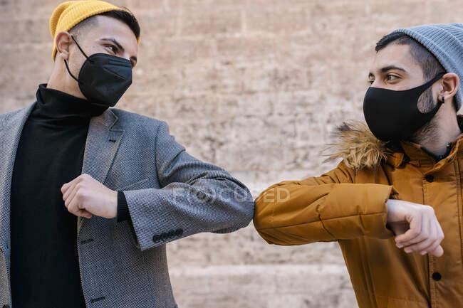 Amigos masculinos usando máscara protetora e chapéu de malha dando colisão no cotovelo enquanto estão de pé contra a parede — Fotografia de Stock