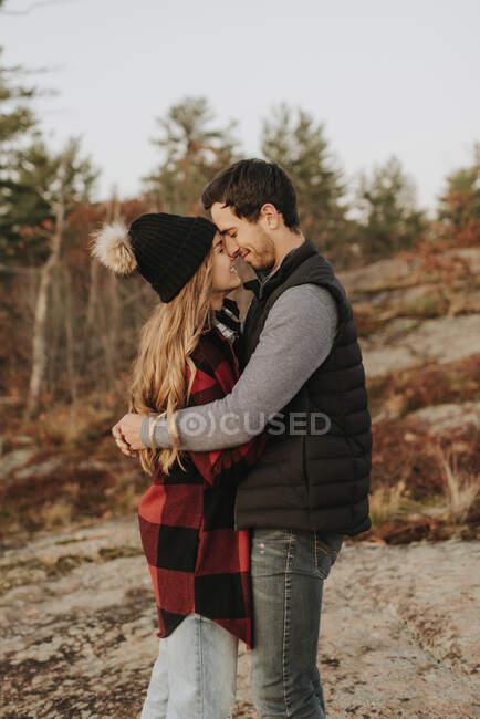 Pareja joven abrazándose durante la caminata de otoño - foto de stock