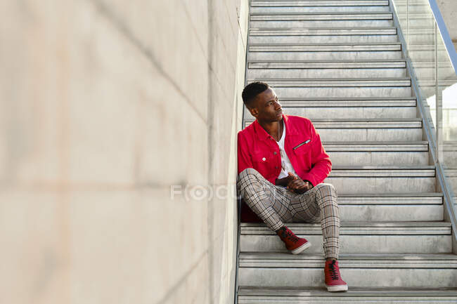 Young man in red jacket and checked pants sitting on steps outdoors - foto de stock