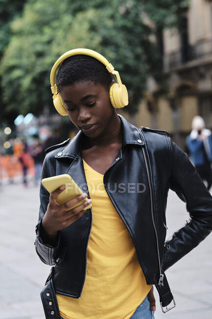 Молода жінка у навушниках, користуючись розумним телефоном, стоячи з міською рукою на стегні. — стокове фото