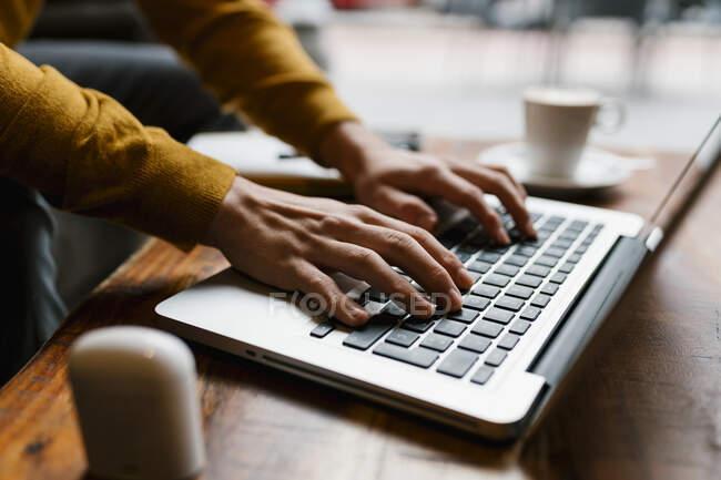 Молодой человек работает на ноутбуке, сидя в кафе — стоковое фото