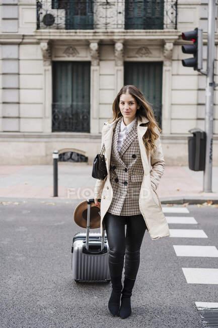 Мовчазна жінка з руками в кишені тягне колісний багаж під час перетину дороги. — стокове фото