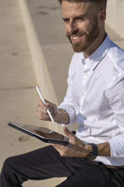 Businessman smiling while using digital tablet sitting on steps — Stock Photo