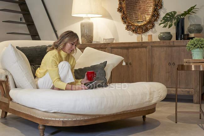 Mujer madura sosteniendo la taza de té mientras que las compras en línea en casa - foto de stock
