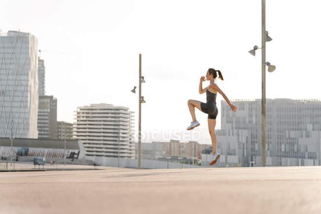 У дорослої спортсменки роблять стрибки у сонячний день у цій місцевості. — стокове фото