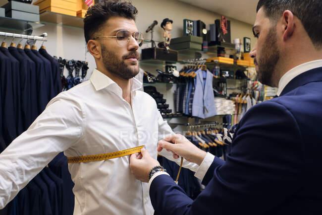 Sarto nel suo negozio di abbigliamento maschile prendendo le misure dei clienti per la tuta — Foto stock