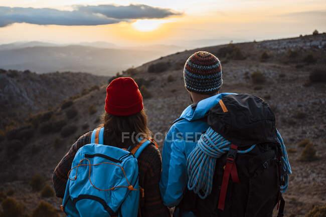 Escursionisti maschi e femmine che si godono il tramonto dalla montagna durante le vacanze — Foto stock