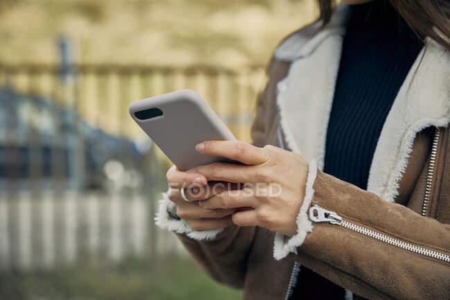 Giovane donna messaggistica di testo tramite telefono cellulare — Foto stock