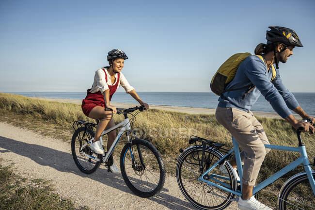 Юна жінка посміхається на велосипеді з чоловіком на стежці проти моря. — стокове фото