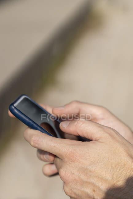 Primer plano del hombre de negocios utilizando el teléfono inteligente al aire libre - foto de stock