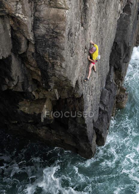 Hombre escalador escalando acantilado de roca - foto de stock