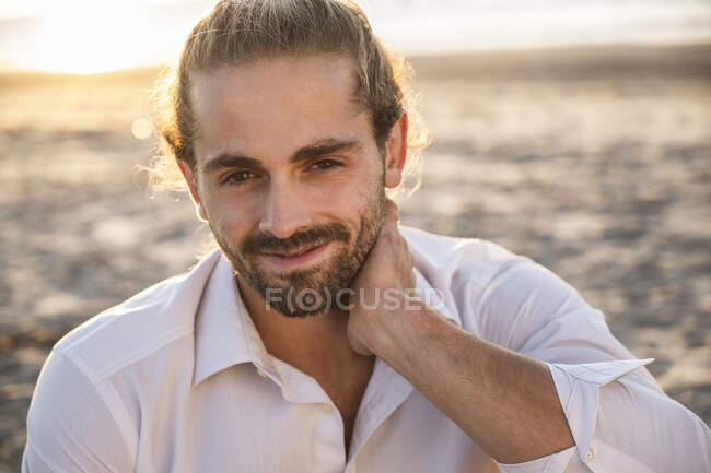 Smiling handsome young man relaxing at beach during sunset - foto de stock