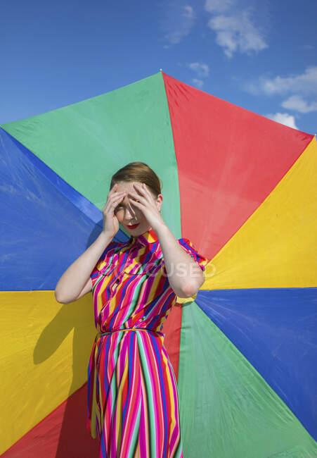Жінка закриває очі, стоячи навпроти барвистої парасольки. — стокове фото