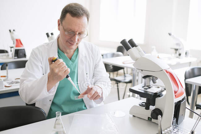 Researcher in white coat working in lab — Stock Photo