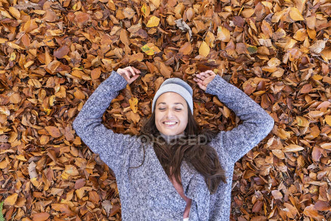Smiling female hiker lying down on autumn leaves in Cannock Chase woodland — Stock Photo