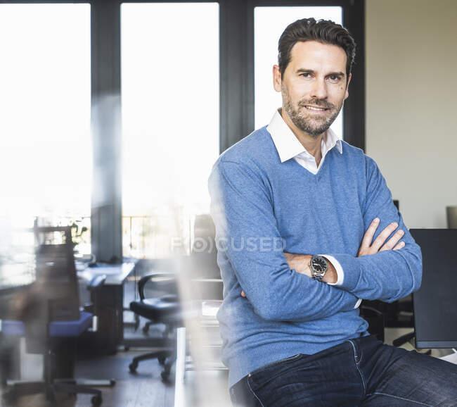Uomo d'affari sicuro seduto con le braccia incrociate in ufficio — Foto stock