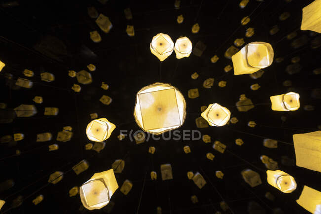 Illuminated design lamps hanging outdoors at night - foto de stock