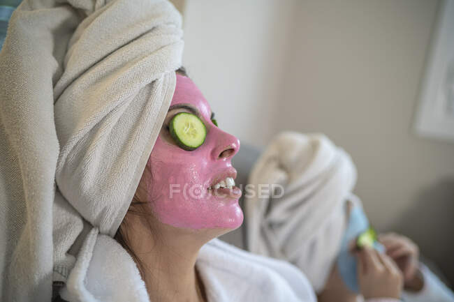 Mother and daughter with facial masks relaxing at home - foto de stock