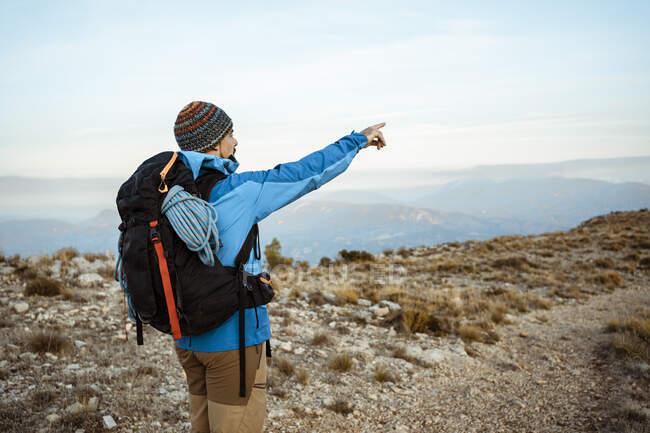 Hombre excursionista señalando mientras mira la vista desde la montaña durante las vacaciones - foto de stock