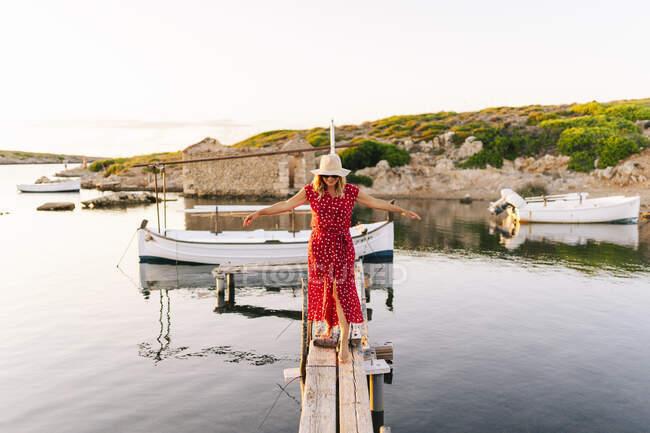 Donna con le braccia tese bilanciamento mentre si cammina sul molo — Foto stock