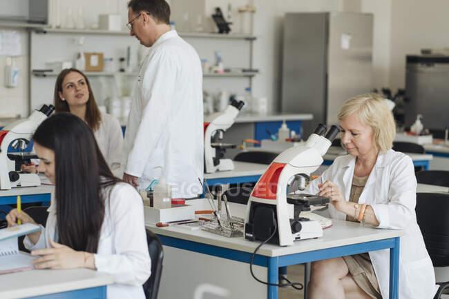Старша жінка-дослідниця в білому пальто працює в лабораторії в оточенні інших дослідників — стокове фото