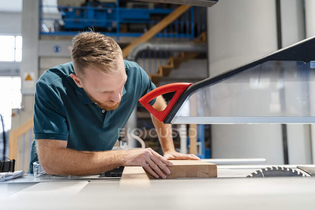 Carpenter cutting plank on circular saw in production hall — Stock Photo