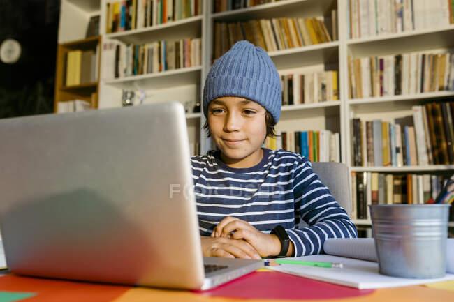 Menino frequentando aula de homeschooling através de laptop à mesa na sala de estar — Fotografia de Stock