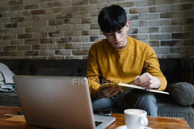 Giovane con computer portatile scrivere in libro mentre seduto sul divano al caffè — Foto stock