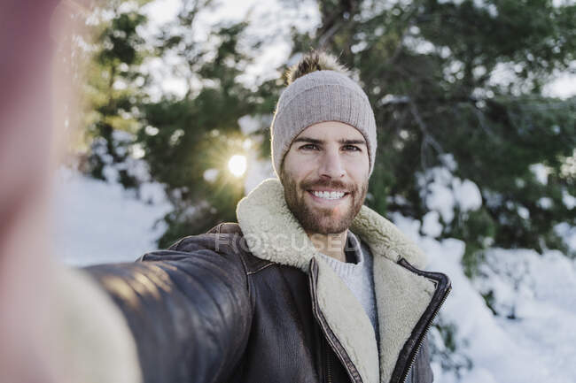 Happy young man taking selfie against trees in cold weather — Stock Photo