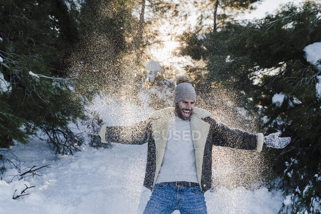 Cheerful man with arms outstretched playing on snow during winter — Stock Photo
