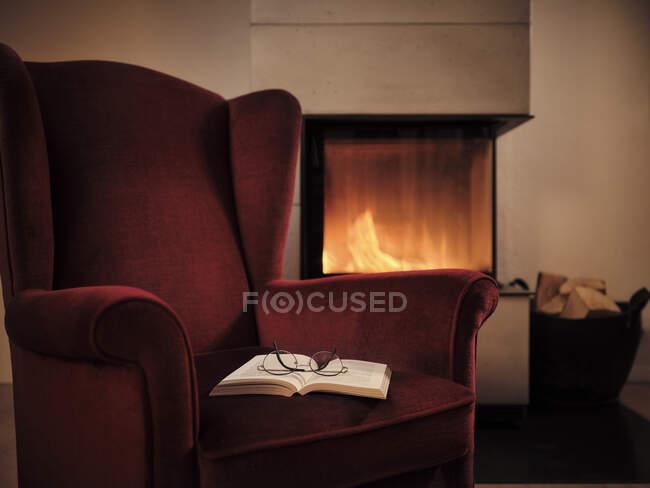 Gafas graduadas con libro abierto en silla wingback marrón junto a chimenea en casa - foto de stock