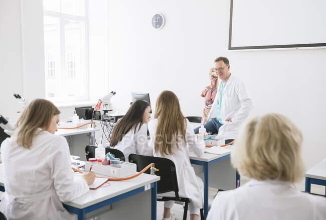 Студенти, які читають лекцію з професором в науковій лабораторії — стокове фото