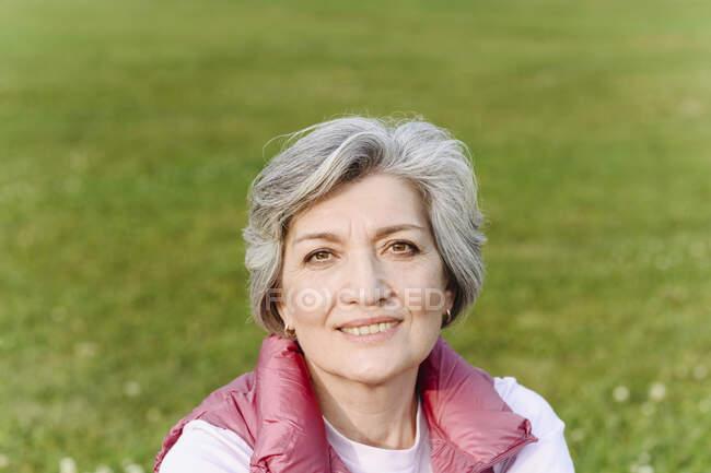 Mujer madura sonriente en el parque público en un día soleado - foto de stock