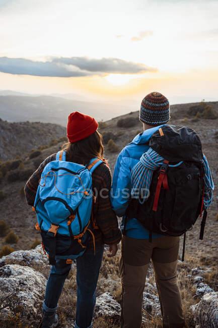 Coppia eterosessuale guardando il tramonto durante le escursioni durante le vacanze — Foto stock