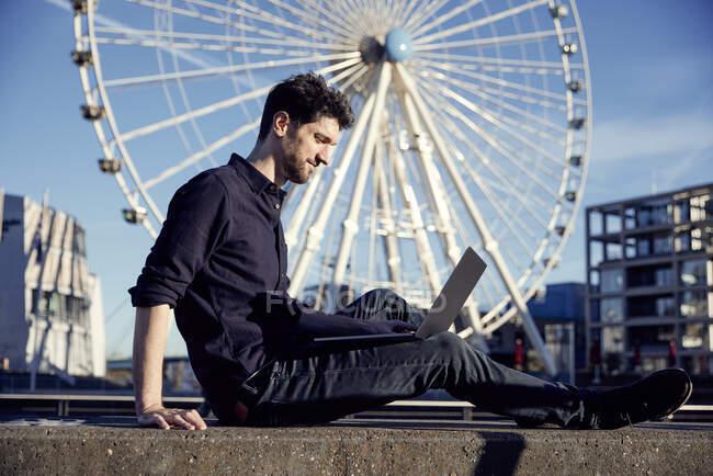Empresario usando portátil mientras está sentado contra la rueda de los hurones - foto de stock